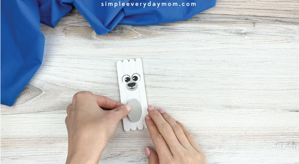 hands gluing belly onto popsicle stick polar bear craft