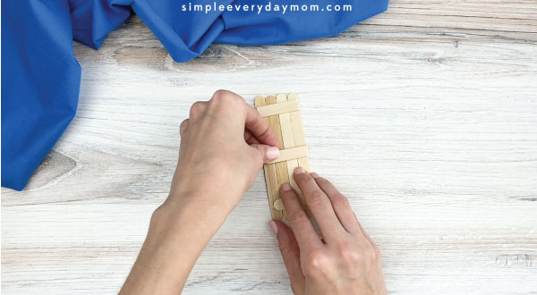 hands gluing popsicle stick together