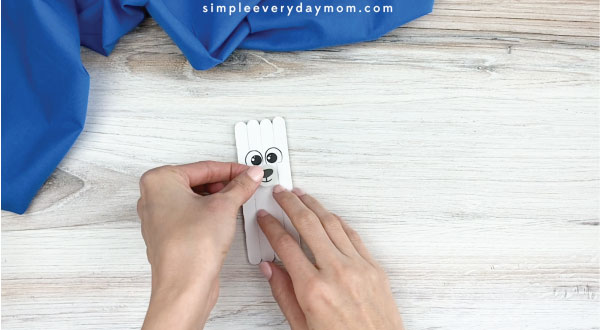 hands gluing mouth and nose onto popsicle stick polar bear craft