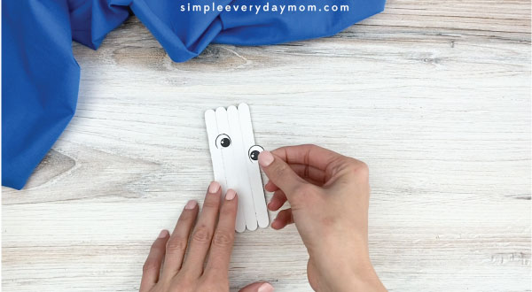 hands gluing eyes onto popsicle stick polar bear craft