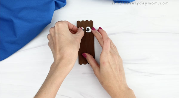 hand gluing eyes onto popsicle stick walrus craft