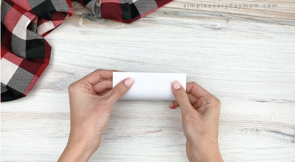 hands wrapping polar bear template around toilet paper roll
