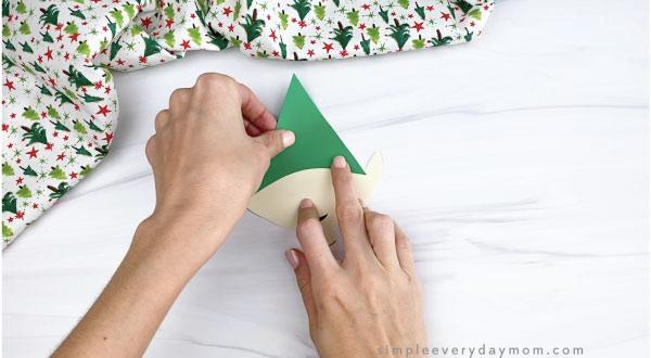 hands gluing hat onto paper elf craft