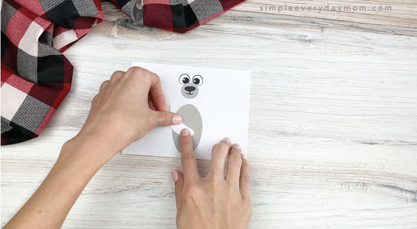 hands gluing arms to toilet paper roll polar bear craft