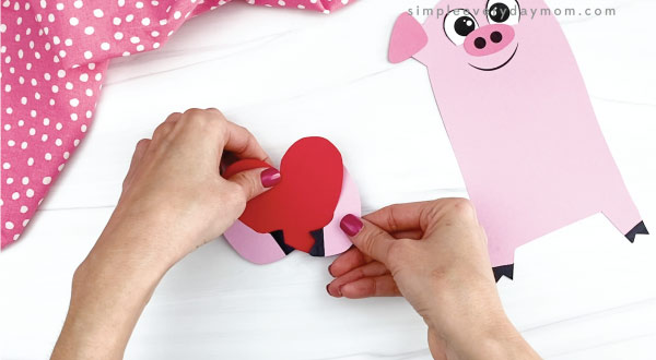 hand gluing pig arms to heart