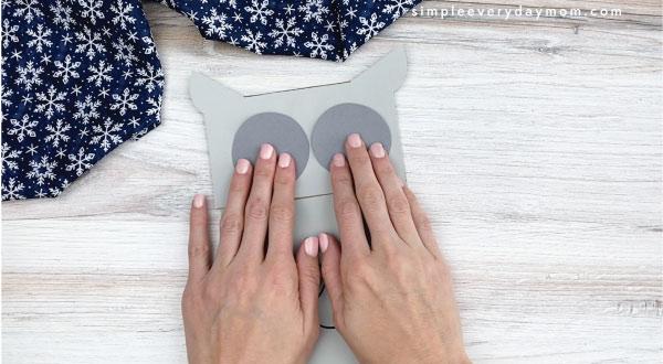 hands gluing gray circles to paper bag owl craft