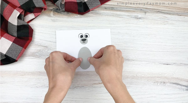 hands gluing belly to toilet paper roll polar bear craft