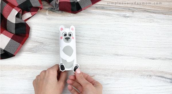 hands gluing feet to toilet paper roll polar bear craft