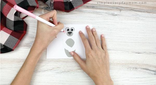 hands drawing cheeks onto toilet paper roll polar bear craft