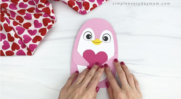 hand gluing arms onto penguin valentine craft