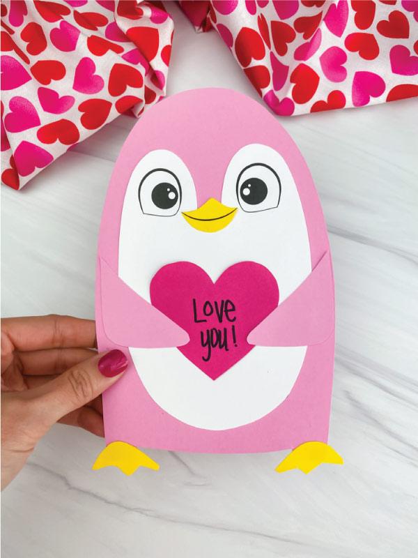 hand holding penguin valentine craft