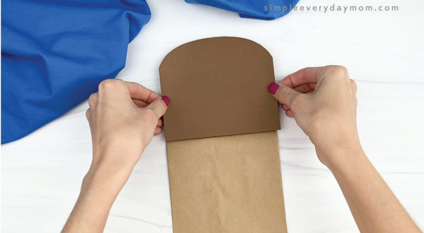 hand gluing head to paper bag walrus craft