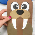 hand holding paper bag walrus craft