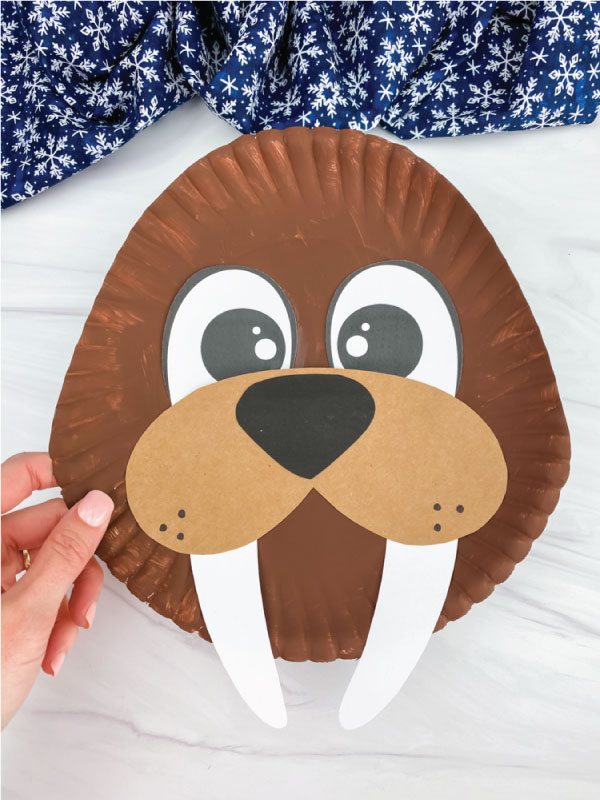 hand holding paper plate walrus craft