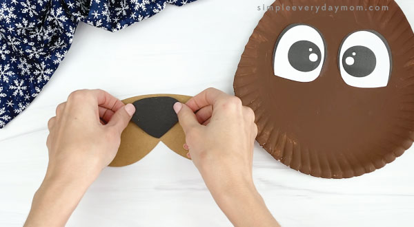 hand gluing nose to paper plate walrus craft