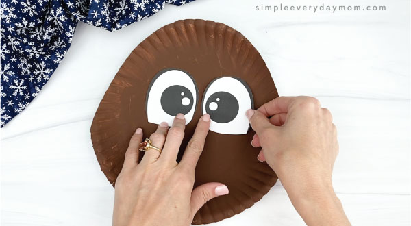 hand gluing eyes to paper plate walrus craft