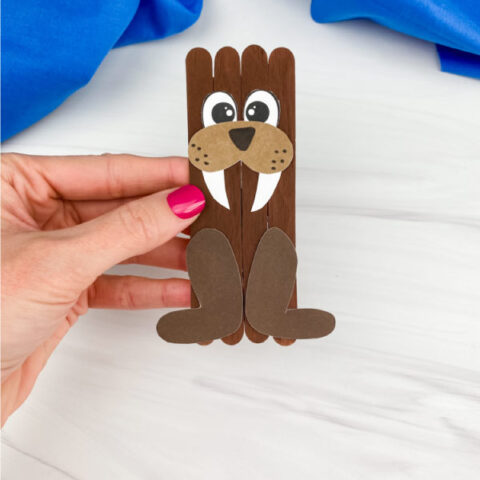 hand holding popsicle stick walrus craft