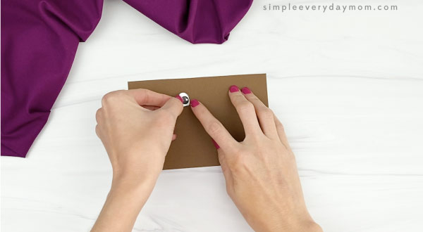 hand gluing eye to toilet paper roll craft