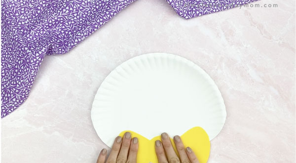 hand gluing bowtie to paper plate Easter bunny craft