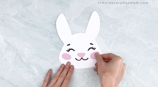 hands gluing cheeks to Easter bunny headband craft
