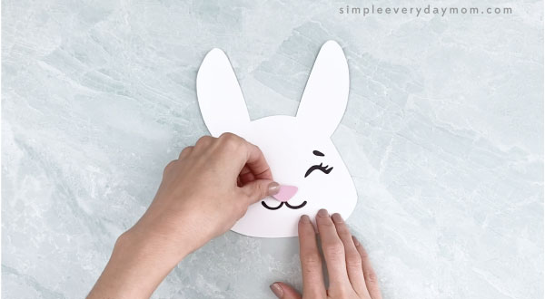 hands gluing nose to Easter bunny headband craft