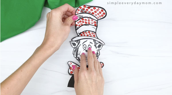 hand gluing hat to cat in the hat craft