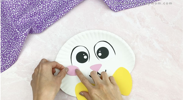 hand gluing cheeks to paper plate Easter bunny craft