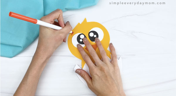 hands drawing eyebrows onto hatching chick craft