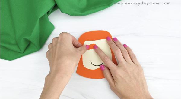 hands gluing eyebrows to leprechaun headband craft