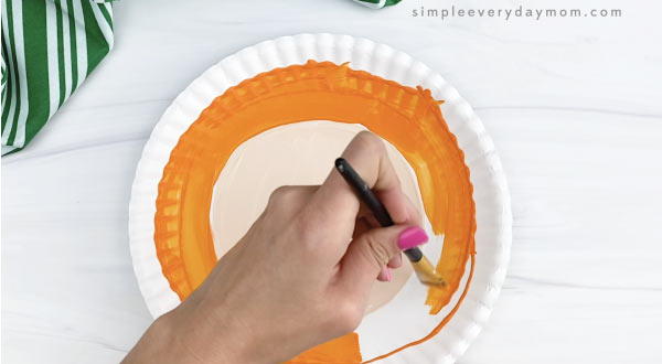 hand painting outer ring of paper plate orange