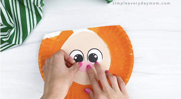 hand gluing nose to paper plate leprechaun craft