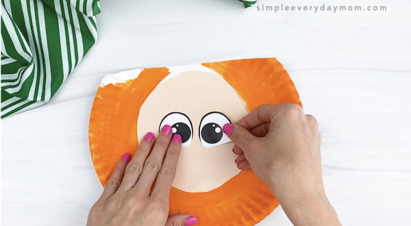 hand gluing eyes to paper plate leprechaun craft