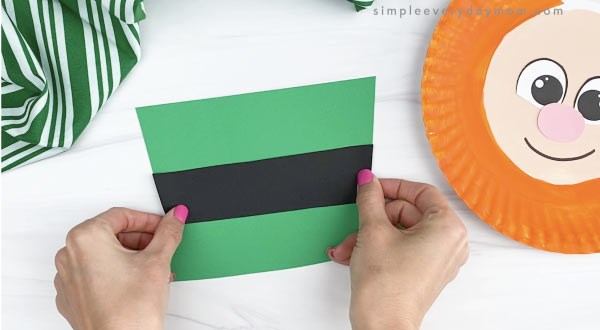 hand gluing black band to paper plate leprechaun hat craft