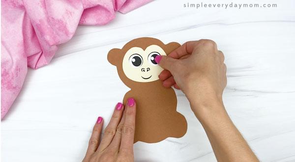 hand gluing eyes to monkey valentine craft