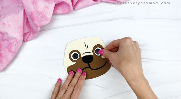 hands gluing eyes onto puppy valentine craft