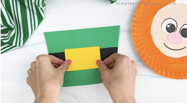 hand gluing yellow buckle to paper plate leprechaun hat craft