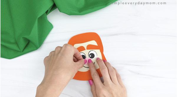 hands gluing nose to leprechaun headband craft