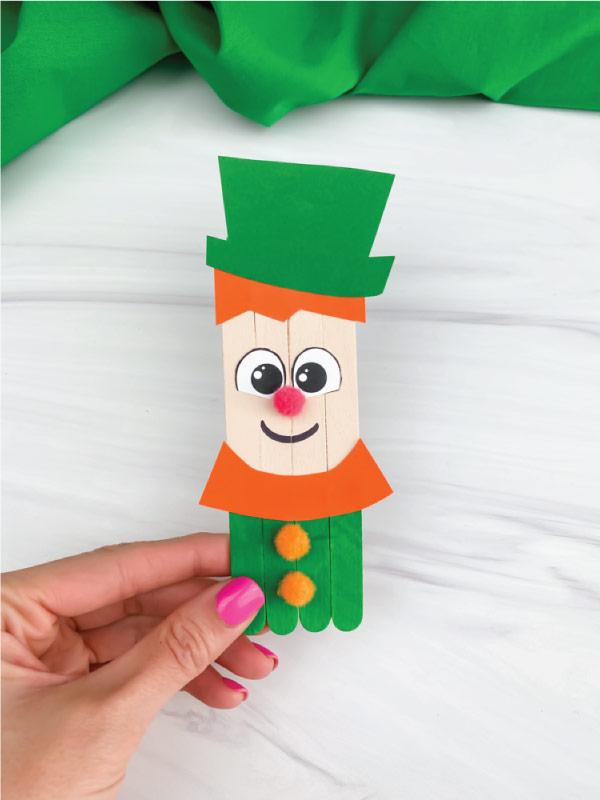 hand holding popsicle stick leprechaun craft
