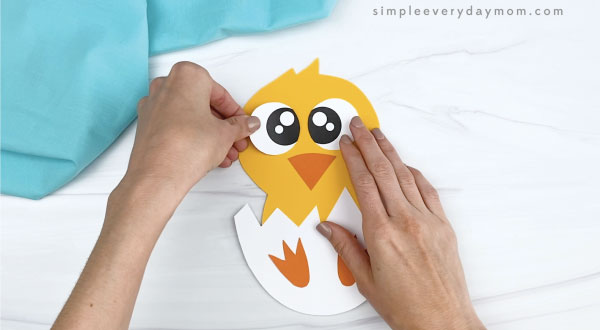 hand gluing eyes onto hatching chick craft