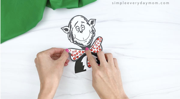 hand gluing bowtie to cat in the hat craft