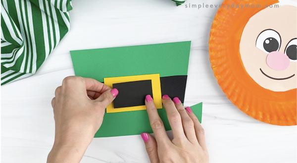 hand gluing black inneer buckle to paper plate leprechaun hat craft
