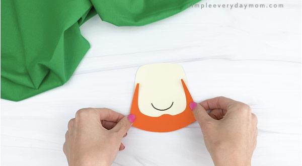 hands gluing beard to leprechaun headband craft