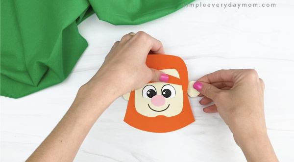 hands gluing ears to leprechaun headband craft