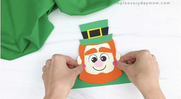 hands gluing head to leprechaun headband craft