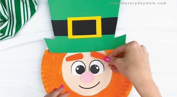 hand gluing eyebrows to paper plate leprechaun craft