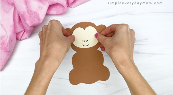 hand gluing face to monkey valentine craft