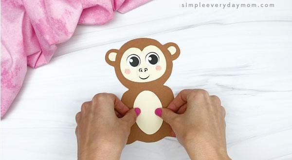 hand gluing belly to monkey valentine craft