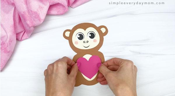 hand gluing heart to monkey valentine craft