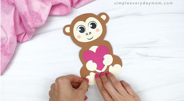 hand gluing feet to monkey valentine craft