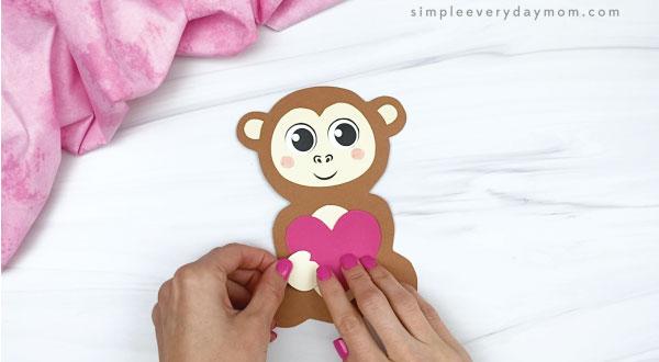 hand gluing hands to monkey valentine craft